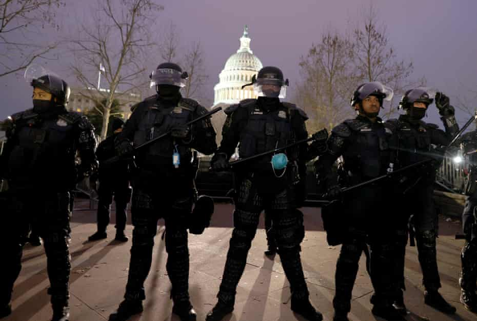 Police officers in riot gear line up near the Capitol building in Washington DC.