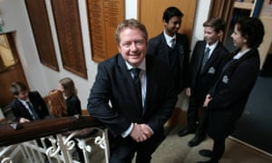 Shaun Fenton on staircase with pupils in background