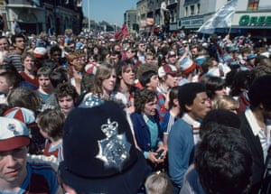Ham United fans wait to see the team during their victory parade after their team won the 1980 FA Cup final