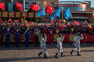 Astronauts Tang Hongbo, Nie Haisheng and Liu Boming wave during a departure ceremony at the launch centre in the Gobi desert.