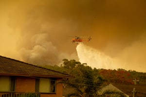 An Aircrane water-bombing helicopter drops water on bushfires in Harrington, on Friday