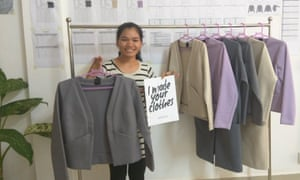 """Woman, holding a jacket and a sign saying """"I made your clothes"""", in front of a clothing rack with jackets on it"""