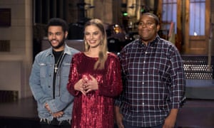 Musical guest The Weeknd, host Margot Robbie, and Kenan Thompson on Saturday Night Live.