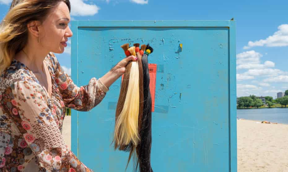 Tatiana 34, holding up several ponytails of hair in different colours that she has cut off.