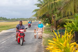 Local people on a road that runs along the side of the airport runway, in central Funafuti