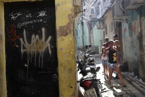 Residents walk near a doorway riddled with bullet holes after a police raid against alleged drug traffickers in the Jacarezinho favela of Rio de Janeiro.