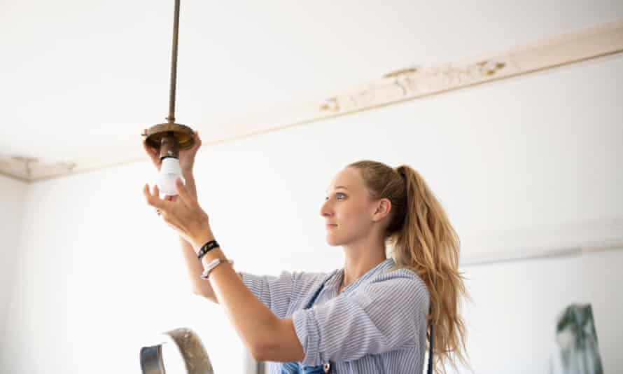 Woman changing a light fixture. Tell us about a five-minute home improvement that has made a big difference.