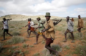 Turkana tribesmen walk with guns to protect cattle in Baragoy, Kenya