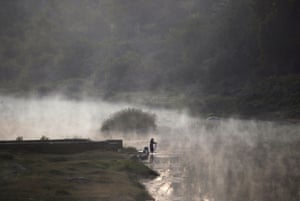A woman washes clothes in the Cauvery, or Kaveri, River in Kushalnagar town, Karnataka, India