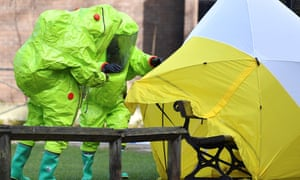 Members of the emergency services in green biohazard encapsulated suits fix the tent over the bench where where former Sergei and Yulia Skripal were found.