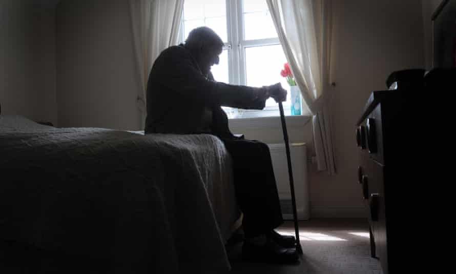 An elderly man silhouetted against a window.
