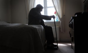 Od man sitting on a bed in a care home
