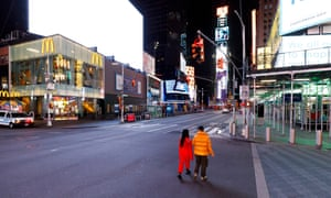 People walk through a nearly empty Times Square in New York.