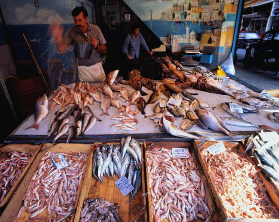 Greece, Crete, Chania, man wetting fish on stall to keep it fresh Also known as Khania, Hania or Canea