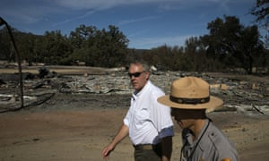 Secretary of the Interior Ryan Zinke, left, visits Paramount Ranch, burned to the ground by the Woolsey fire, in California. He said of climate change warnings: 'If you take the extreme case, you're right, it's dire. If you take the best case, it's not much.'