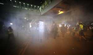 Riot police fire tear gas as they arrive to disperse protesters from the Legislative Council building.