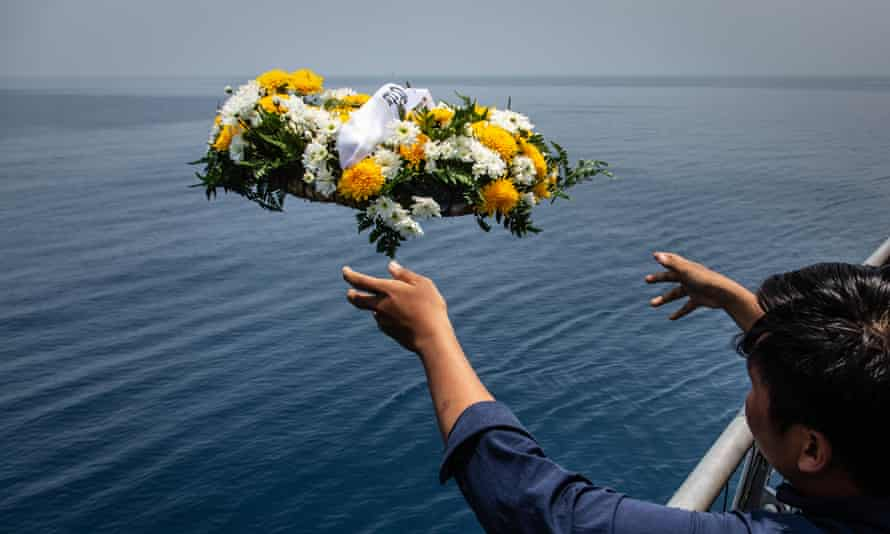 Mourner throws flower wreath into the sea