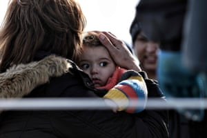 A mother holds her child as a Greek coastguard boat rescues people at the port of Mytilene