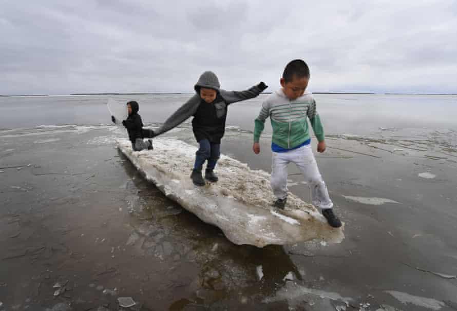 Children play on melting ice near the Yupik Inuit village of Napakiak on the Yukon Delta.