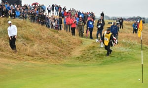 Rory McIlroy watches his ball approach the hole after chipping out of the rough onto the 2nd green.