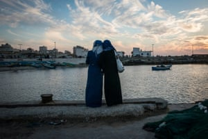 Girls watch the sun set at the harbour in Gaza City