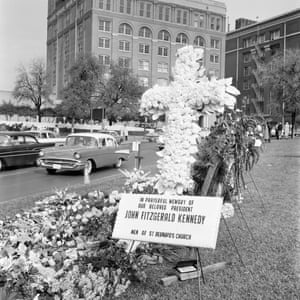 A memorial at the scene of Kennedy's assassination. In the background is the Texas School Book Depository.