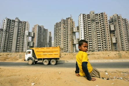 A boy sits with the backdrop of a residential complex in Gurgaon, India