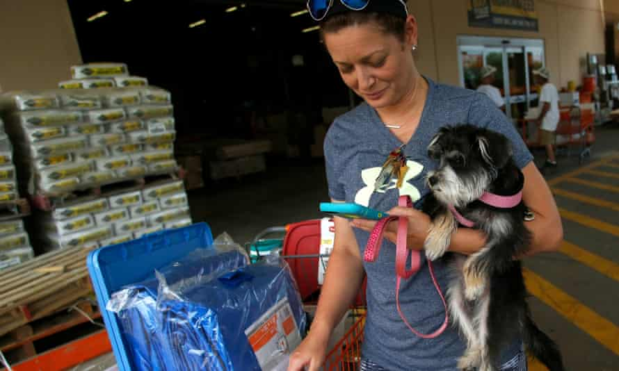 Michelle Smith checks her smart phone for news while clutching her dog Sophia as she leaves a Home Depot store with storm preparation supplies in Tampa.