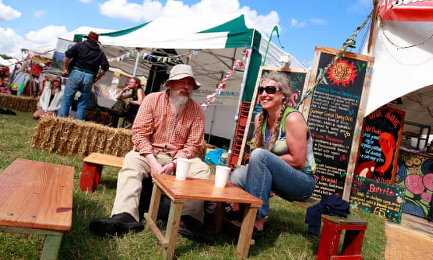 A couple sit dining at outside bench seats at the Shambala festival, 2015, in Northamptonshire.