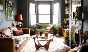 The front room with dark grey walls, a large Victorian bay window at the end, a sofa and coffee table and Victorian fireplace