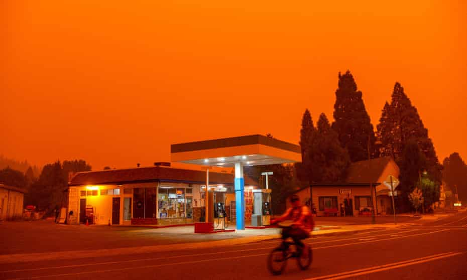 A man rides his bike past a gas station as smoke fills the sky in Greenville, California last week. The Dixie fire has become the largest in California after it exploded in size over the weekend.