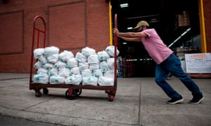 Unemployed construction worker Felix Pinzon pushes a cart of food delivery donations in the Bronx.