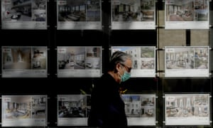 a man with a face mask passes an estate agent window