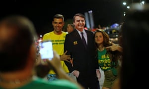 Supporters of Jair Bolsonaro pose with a cardboard cutout of him in Brasilia.