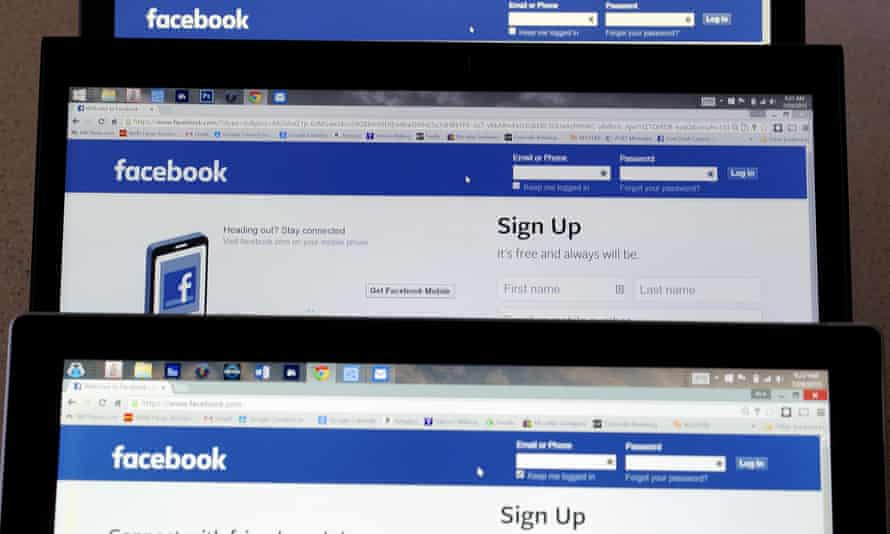 Computer screens display the Facebook sign-in screen