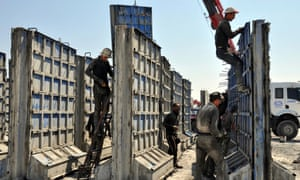 Turkish workers with some of the modular blocks that will form the wall along the Syrian border