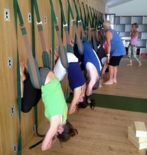 Jane Dunford, nearest the camera, in 'child pose' on the yoga wall