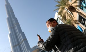 A man wears a protective mask while taking a picture of the world's tallest building, Burj Khalifa, in Dubai, United Arab Emirates.