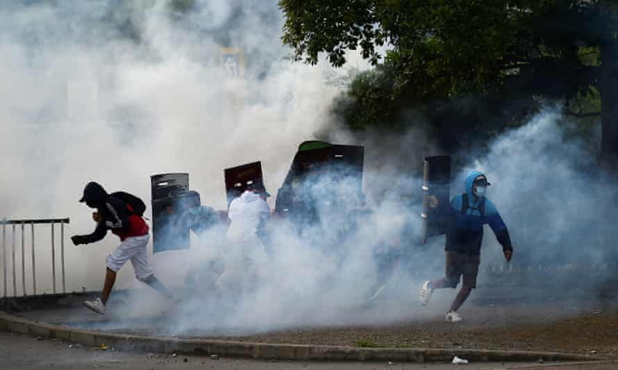 Teargas rises around demonstrators in Cali, Colombia.