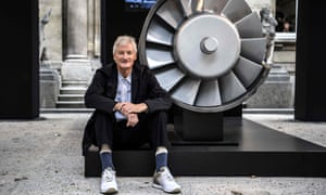 James Dyson poses next to the model of an engine.