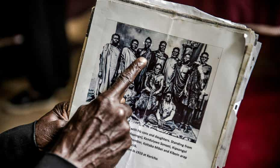 A man affected by the forcefully evictions shows a picture of his relatives and ancestors