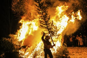 Eagle, US. A man tosses a tree on a bonfire as part of an annual Twelfth Night tradition