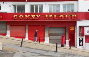 An older man walks past the closed Coney Island amusement arcade in Scarborough