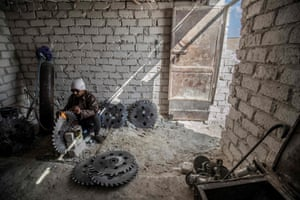 A man sitting and working on a round saw blade