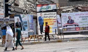 Voters walk past election campaign posters on their way to a polling station in Mosul