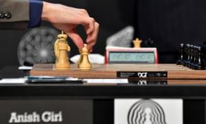 Grandmaster Anish Giri moves chess piece