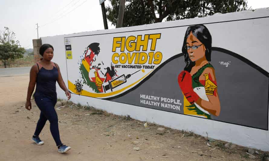A woman walks past a mural encouraging people to get vaccinated against Covid-19 in Epworth, Harare, Zimbabwe, August 2021