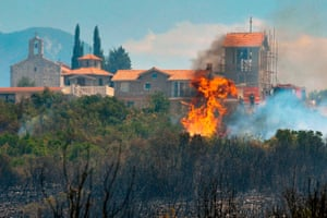 A forest fire consumes trees next to a monastery on the Lustica Peninsula near the town of Tivat, Montenegro