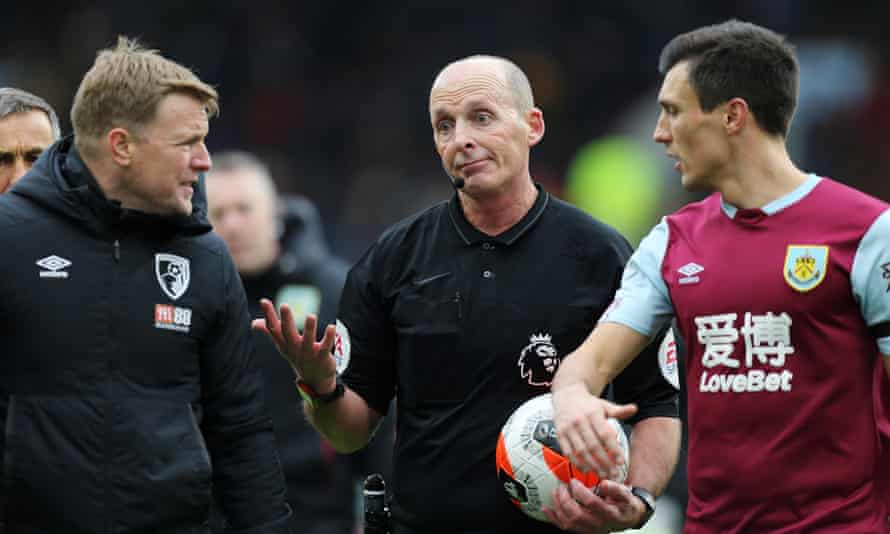 Mike Dean (centre) offers his verdict at half-time on the VAR decision against Bournemouth that enraged Eddie Howe (left) in the defeat by Burnley on Saturday.