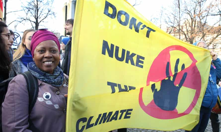 protester with sign saying 'don't nuke the climate'